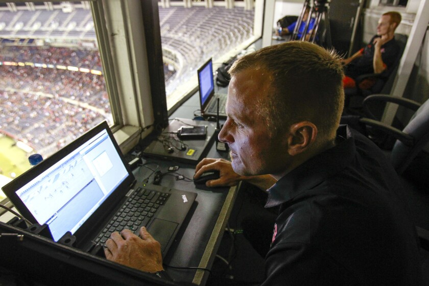 During halftime, Brian Murphy, video coordinator for SDSU, edits game action video from the Aztecs game against San Jose State on a computer while in a booth at the top of at Qualcomm Stadium.