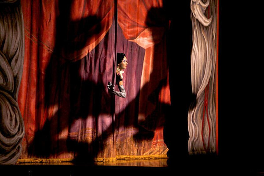 """A performer peeks through the curtain in a scene from """"Iris,"""" a show about Hollywood by Cirque du Soleil. The production will end its run in January following disappointing ticket sales."""