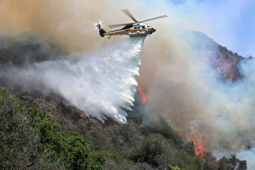 A helicopter drops water onto a fire in Topanga Canyon.