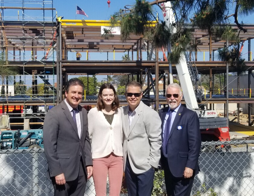 Lee Dulgeroff (chief facilities planning and construction officer), Ila Komasa (Point Loma High School ASB president and a senior), principal Hans Becker and Michael McQuary (a San Diego Unified Board of Education trustee) commemorate a construction milestone for the new, three-story 800 Building; as the final beam — painted gold in support of PLHS colors (maroon and gold) — is lowered into place.