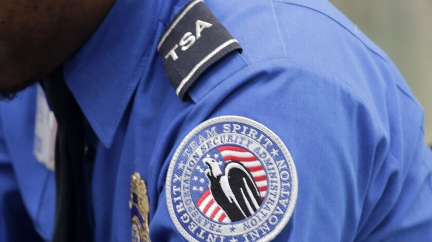 In this photo taken Oct. 30, 2014, a TSA shoulder patch is shown on the uniform of a Transportation