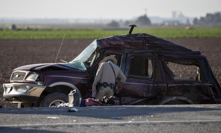 An officer looks inside driver side window of a wrecked vehicle