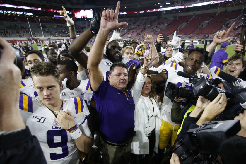 LSU coach Ed Orgeron celebrates with his players after defeating Alabama 46-41 on Saturday.