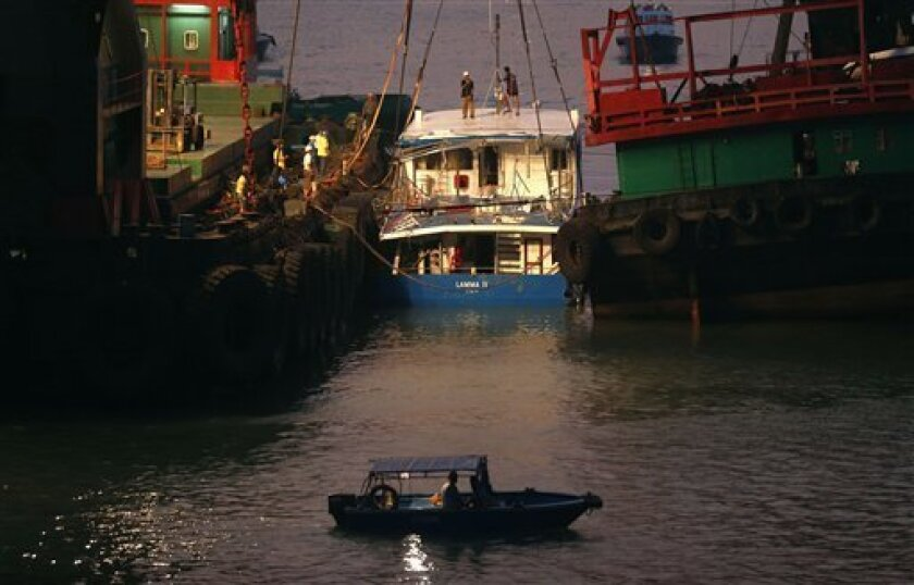 Workers check on a salvaged boat that sank the previous night after colliding with a ferry near Lamma Island, off the southwestern coast of Hong Kong Island, Tuesday, Oct. 2, 2012. The boat packed with revelers on a long holiday weekend sank, killing nearly 40 people and injuring dozens, authorities said. (AP Photo/Kin Cheung)