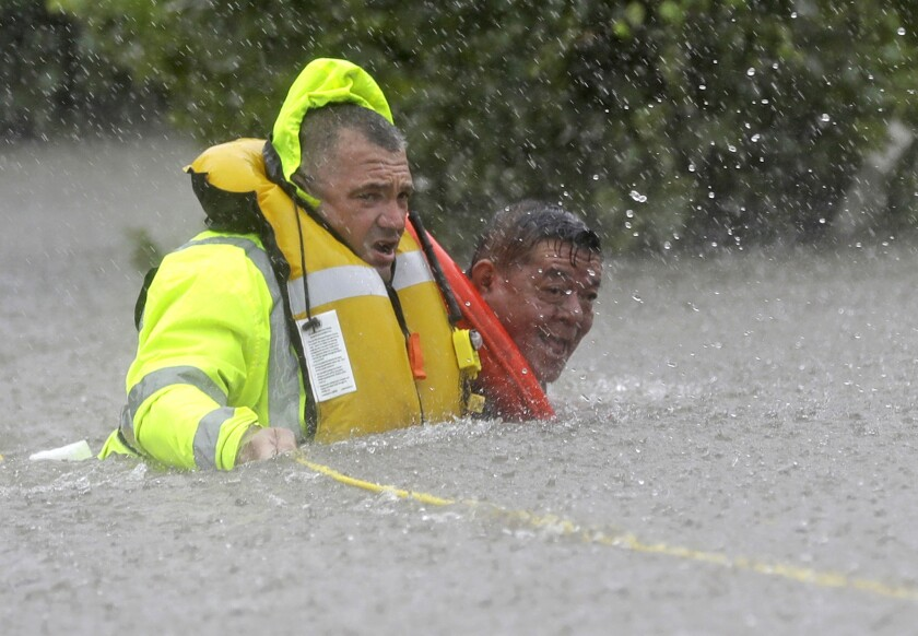 Wilford Martinez, right, is rescued from his flooded car by Richard Wagner of the Harris County Sheriff's Department along Interstate 610 in floodwaters from Tropical Storm Harvey on Sunday.