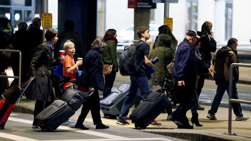 FILE - In this Nov. 26, 2014, file photo, passengers leave a departure area after arriving at Logan