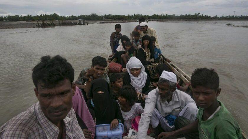 Rohingya refugees cross into mainland Bangladesh on Sunday after fleeing Myanmar.