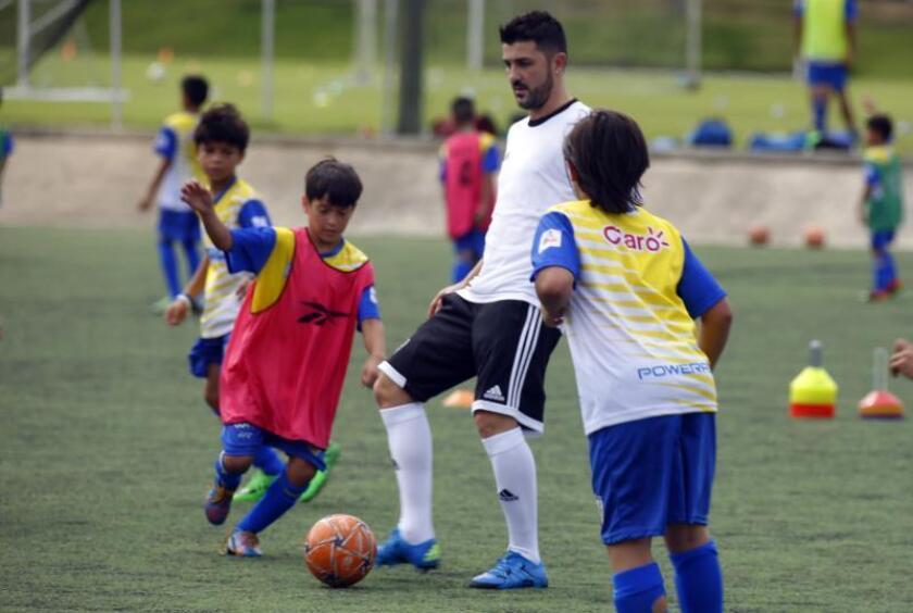 El futbolista español David Villa (c) juega con niños durante la inauguración de la Academia de Fútbol David Villa, el domingo 17 de enero de 2016, en Bayamón (Puerto Rico). EFE/Thais Llorca/Archivo