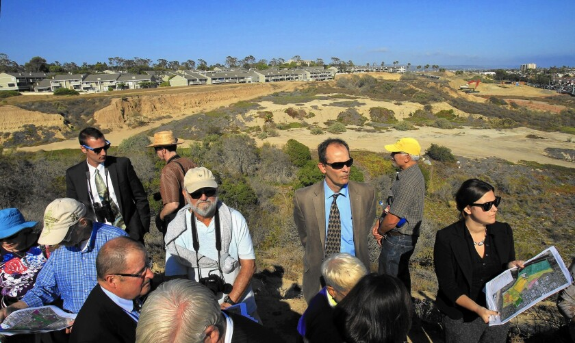 Charles Lester, executive director of the California Coastal Commission, center in suit and tie, tours a project near Newport Beach. News broke last week that some commissioners are angling to oust him from his position.