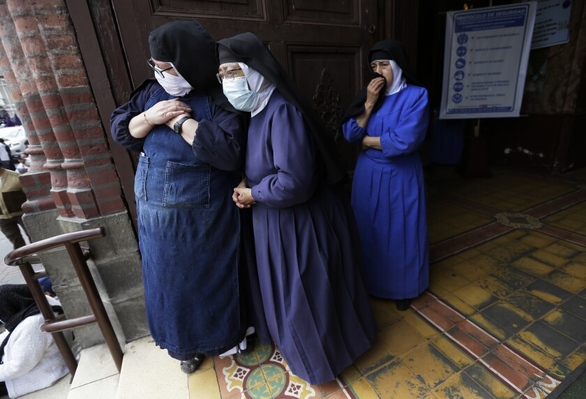 Nuns watch from the doorway of a church as the statue of the Lord of Good Success leads the Holy Week procession in Riobamba, Ecuador, Tuesday, March 30, 2021. Due to the COVID-19 pandemic, the sacred image did not have the crowds that usually accompany it in the procession. (AP Photo/Dolores Ochoa)
