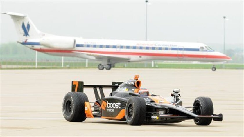 IRL driver Danica Patrick shows off her new IndyCar for the media on the tarmac at the Indianapolis International Airport in Indianapolis on Friday, May 1, 2009. (AP Photo/Tom Strickland)
