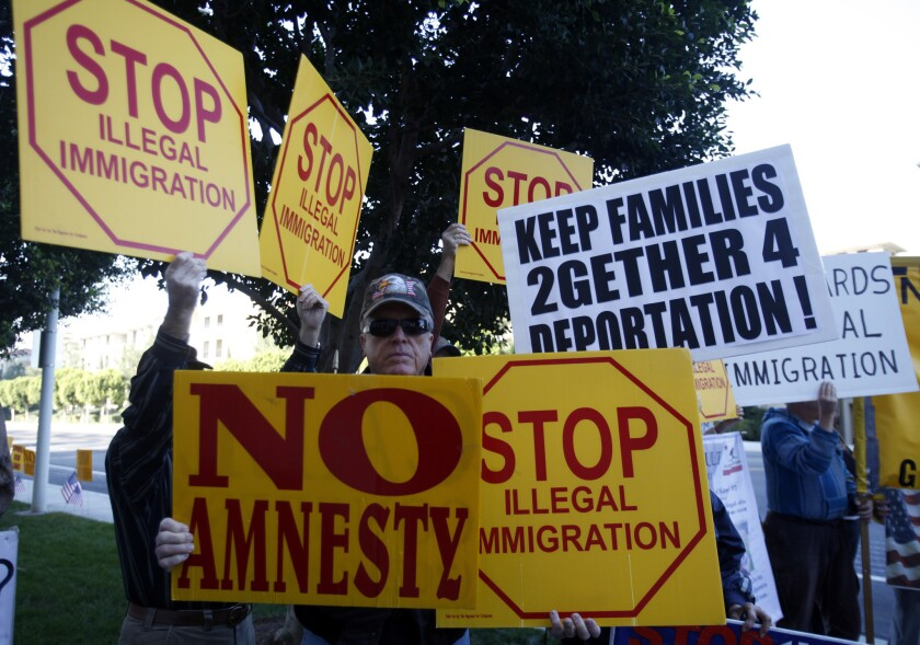 "An anti-immigration group rallies in Irvine in 2013. Many such groups prefer to use the term ""illegal alien."""