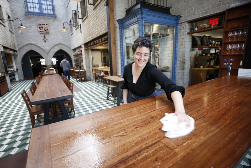 Restaurant manager Grace Curran wipes tabletops with disinfectant at Republique.