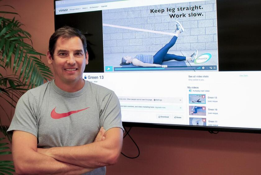 Physical therapist Juan Reque poses in his Solana Beach office in front of a monitor displaying one of his new injury-prevention videos for PreventOK, www.preventok.com