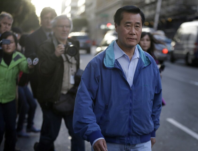 California Sen. Leland Yee, D-San Francisco, right, leaves the San Francisco Federal Building, Wednesday, March 26, 2014, in San Francisco.  The FBI has filed a 137-page affidavit outlining a detailed corruption case against Yee, who is accused of asking for campaign donations in exchange for intro