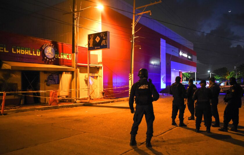 Police officers stand guard outside Caballo Blanco (White Horse) bar where 27 people were killed by a fire