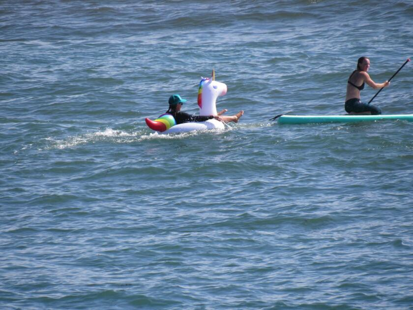 Enjoying the ocean in a white unicorn float