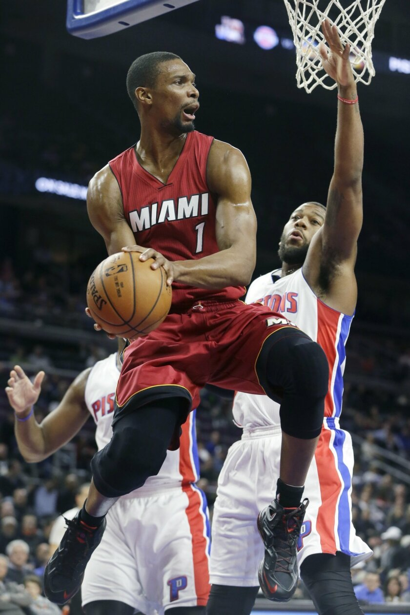 FILE - In this Feb. 3, 2015, file photo, Miami Heat center Chris Bosh passes around the defense of Detroit Pistons forward Greg Monroe during an NBA basketball game in Auburn Hills, Mich. Bosh says he will have further exams on his strained right calf when he returns to Miami, trying to determine t