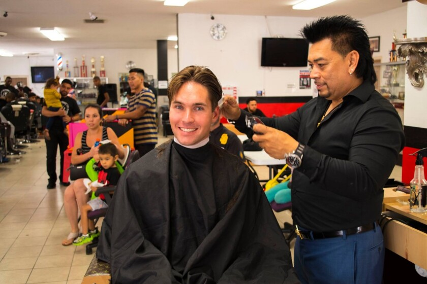 Miles Himmel gets a trim from barber college owner Danny Nguyen during the 2019 back-to-school event.