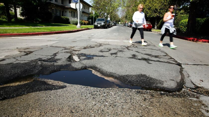 HANCOCK PARK, CA-APRIL 22, 2013: Pedestrians walk near a pothole in need of repair at the intersecti