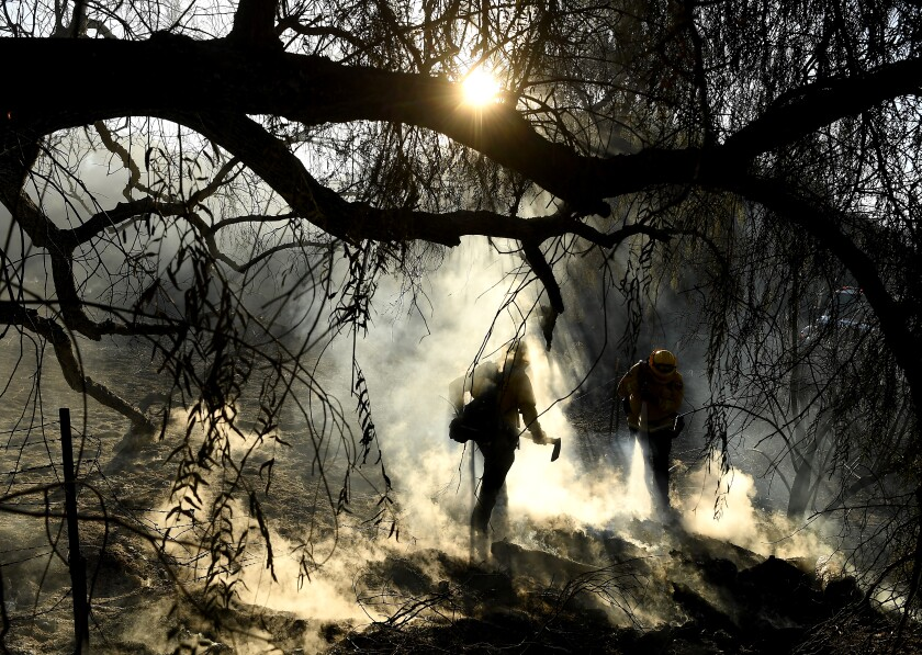 Firefighters extinguish hot spots  along Santiago Canyon Road in unincorporated Orange County.