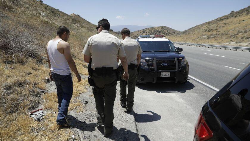 LOS ANGELES, CA -- JULY 03, 2018: Los Angeles Sheriff's Deputies Michael Vann, center, and John Leit