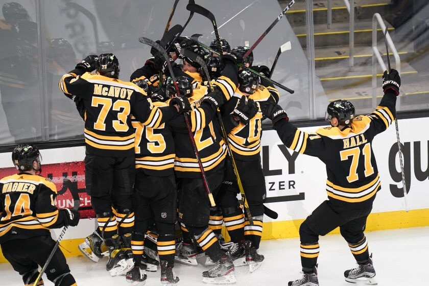 Teammates surround Boston Bruins right wing Craig Smith after his game-winning goal against the Washington Capitals during a second overtime period of Game 3 of an NHL hockey Stanley Cup first-round playoff series, Wednesday, May 19, 2021, in Boston. The Bruins won 3-2. (AP Photo/Charles Krupa)