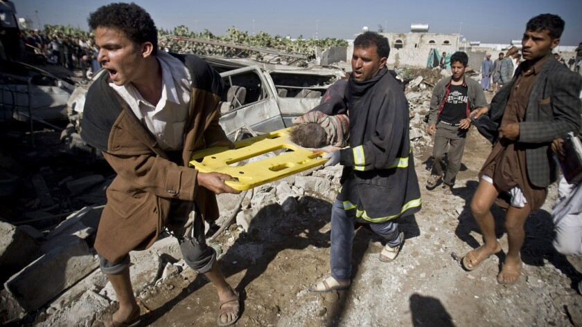 Men carry the body of a child uncovered from the rubble of houses destroyed by Saudi airstrikes near Sana's international airport in Yemen on March 26.