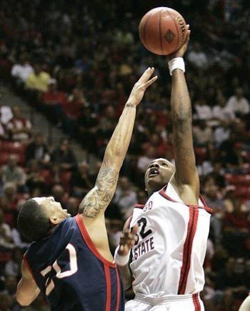San Diego State's Billy White goes over St. Mary's defender Diamon Simpson in a matchup of big men. White led the Aztecs with 17 points.