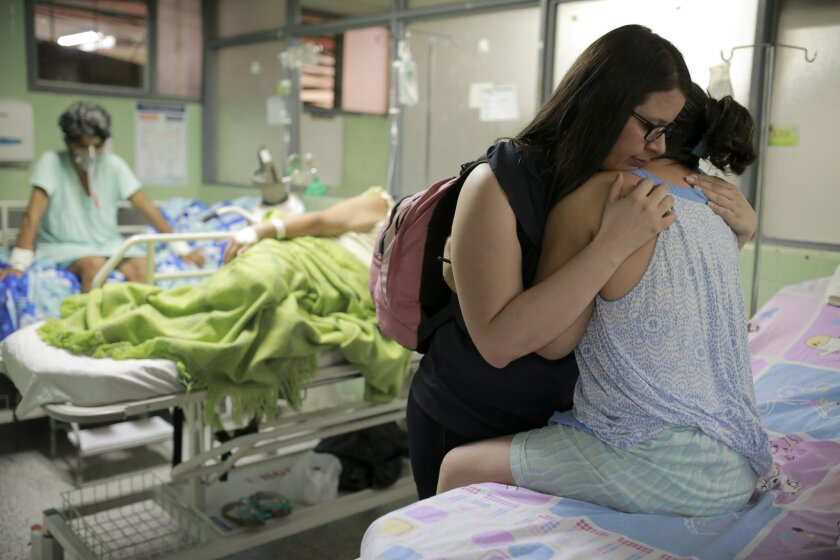 Xiojanni Badillo embraces her aunt Daysi Mendoza who's recovering from Gullain-Barre syndrome, a disorder in which the immune system attacks nerve cells, at the Erasmo Meoz Hospital in Cucuta, Colombia, Thursday, Feb. 11, 2016, a city on the border with Venezuela. Mendoza, a Venezuelan who crossed