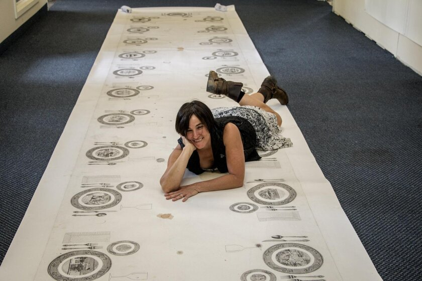 """Iana on her 30-foot-long Tijuana-themed graphite-on-paper tablecloth, actually used at the reception for her 2008 show at CECUT. Each plate represents one of TJ's historic sites. """"Research and mapping are my tools of conquest,"""" she said."""