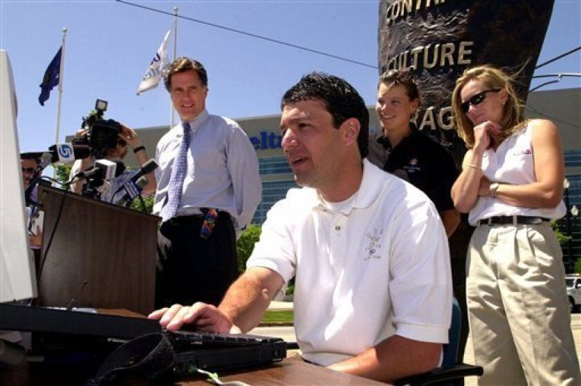 FILE - In this May 31, 2000 file photo, Olympic medalist Andy Gabel demonstrates how to purchase 2002 Winter Game tickets via the Internet during a news conference in Salt Lake City. Looking on is Salt Lake Organizing Committee president Mitt Romney, left, and Olympic medalists Hilary Lindh and Denise Parker, right. U.S. Speedskating began an investigation Friday, March 1, 2013, into the report of a female skater accusing former Olympian and organization president Andy Gabel of sexual abuse in