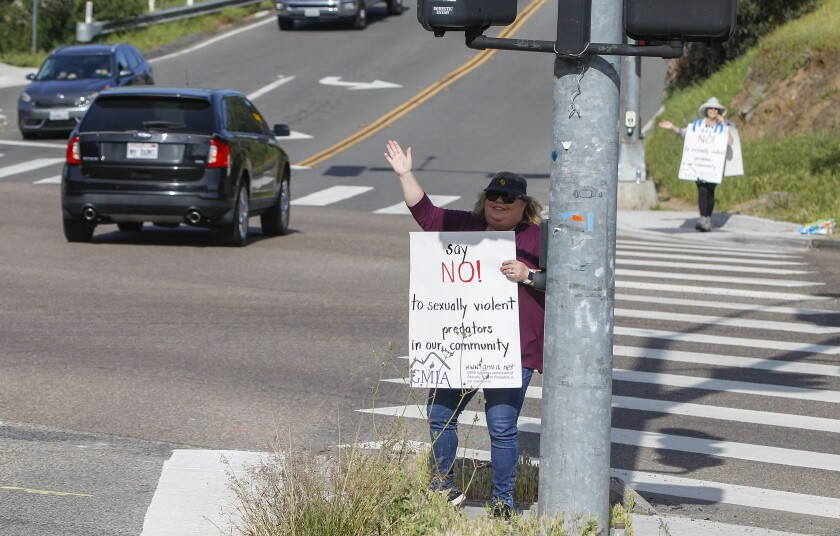 Kathleen Hedberg protests and carries a sign Tuesday opposing proposed placement of sexually violent predator Douglas Badger