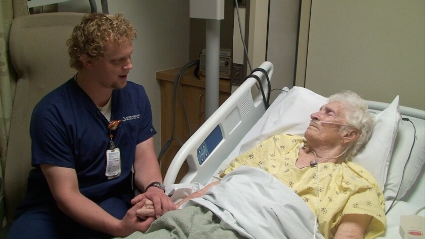 Jared Axen, dubbed the singing nurse, serenades Norma Laskoske, a patient at Henry Mayo Newhall Hospital.