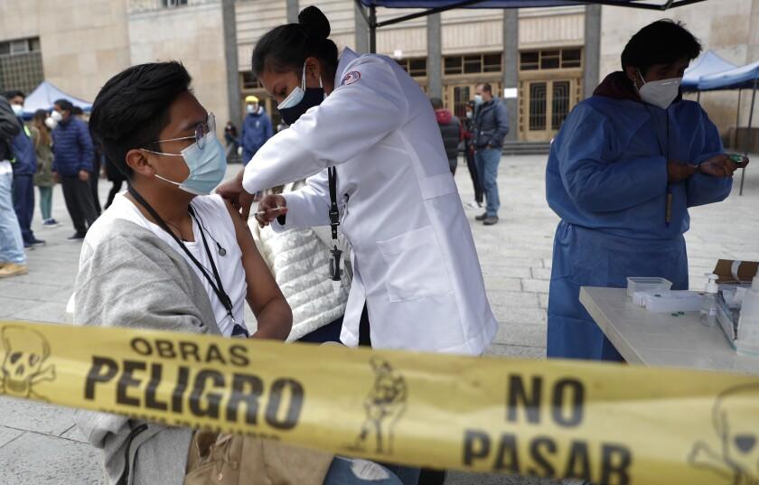 Una estudiante que ayuda a los trabajadores de la salud con las vacunas COVID-19 recibe una inyección de la vacuna AstraZeneca en la universidad pública Universidad Mayor de San Andrés en La Paz, Bolivia, el viernes 9 de abril de 2021. La Organización de Estados Americanos y la Organización Panamericana de la Salud denunciaron el miércoles la crítica situación que atraviesan los países de Latinoamérica por la desigualdad en el acceso a las vacunas contra el COVID-19. (Foto AP/Juan Karita)