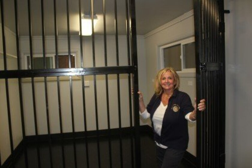 Rotarian and La Jolla Town Council member Nancy Gardner stands next to a holding pen for police beach cruisers (not people, she assures) inside the newly remodeled police storefront.