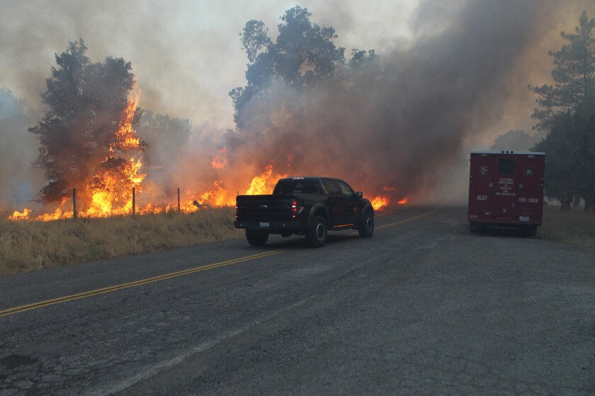 A truck makes its way Friday past the Bully fire near Ono, Calif. A man is facing an involuntary man slaughter charge in connection with the fire.