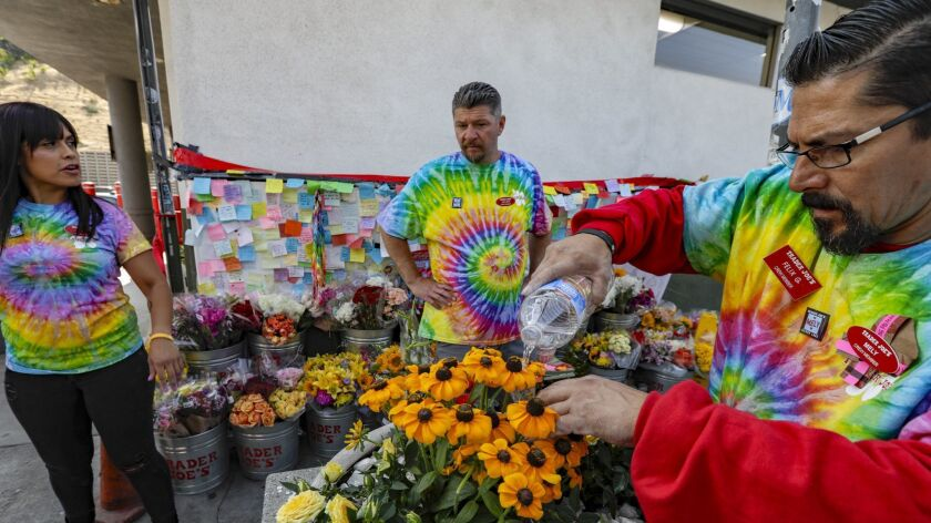 Trader Joe's employees wear tie-dye T-shirts in memory of their slain co-worker, Melyda Corado, on Thursday, the first day the store was open since the July 21 shootout.