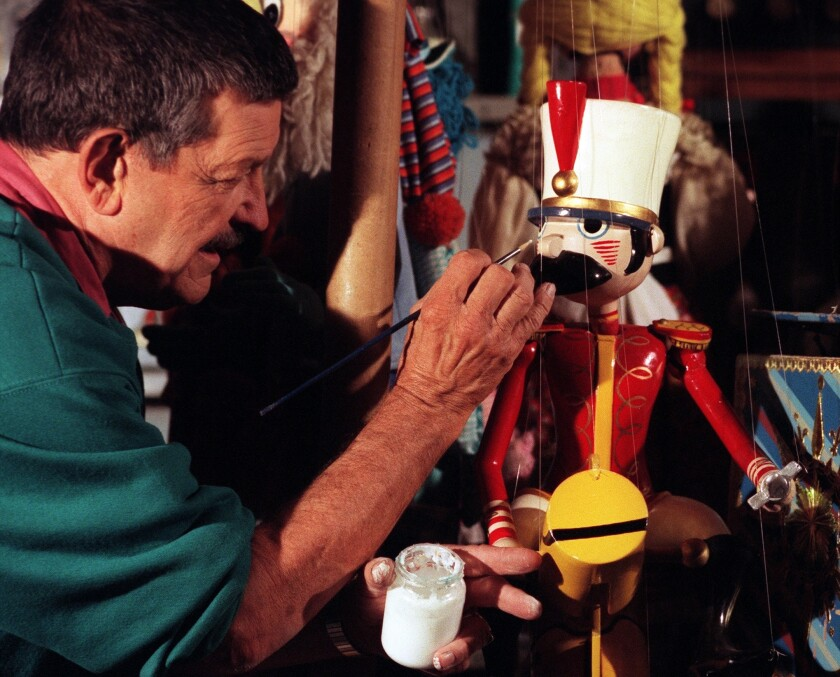 In this 1998 photo, Bob Baker repairs one of his puppets backstage at his Marionette theater.