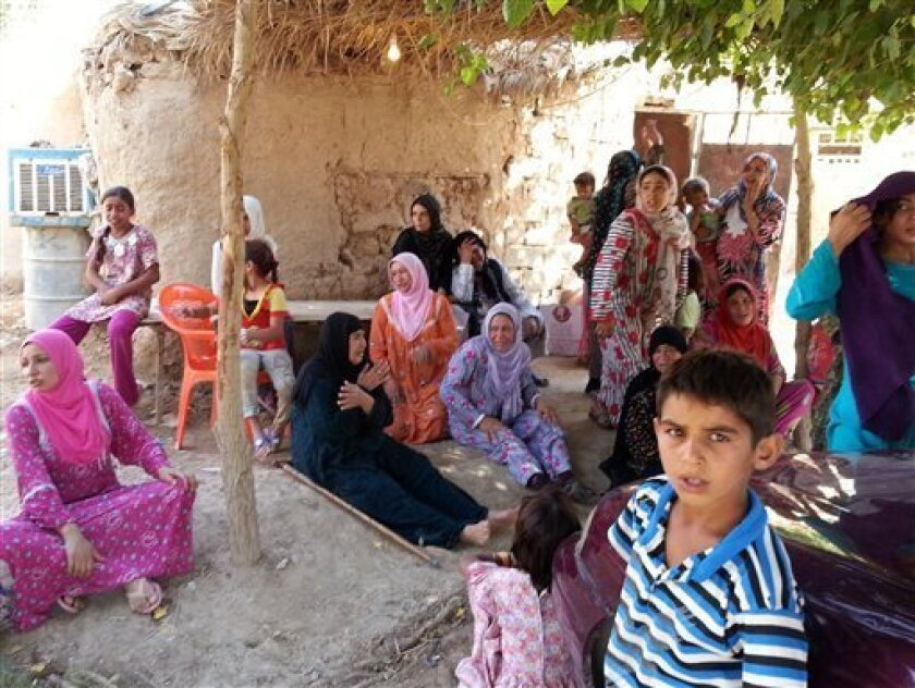 Iraqi women and children gather outside of a Sunni mosque after a suicide bomber struck during Friday prayers in the village of Umm al-Adham in Diyala province, a former militant stronghold 60 kilometers (35 miles) northeast of Baghdad, Iraq, Friday, Sept. 13, 2013. Iraq is weathering it deadliest bout of violence in half a decade, raising fears the country is returning to the widespread killing that pushed it to the brink of civil war following the 2003 U.S.-led invasion.(AP Photo)