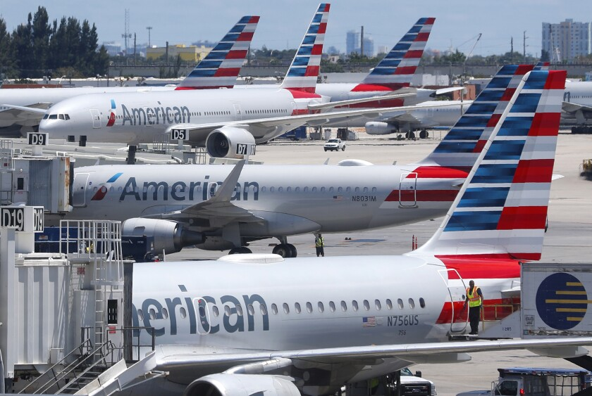 FILE - In this April 24, 2019, photo, American Airlines aircraft are shown parked at their gates at Miami International Airport in Miami. A veteran airline mechanic has been sentenced to three years in prison for sabotaging an American Airlines jetliner in Miami with 150 people aboard. The lawyer for 60-year-old Abdul-Majeed Marouf Ahmed Alani said at a hearing Wednesday, March 4, 2020, that the mechanic's sole motive in July was to earn overtime fixing the plane. (AP Photo/Wilfredo Lee, File)