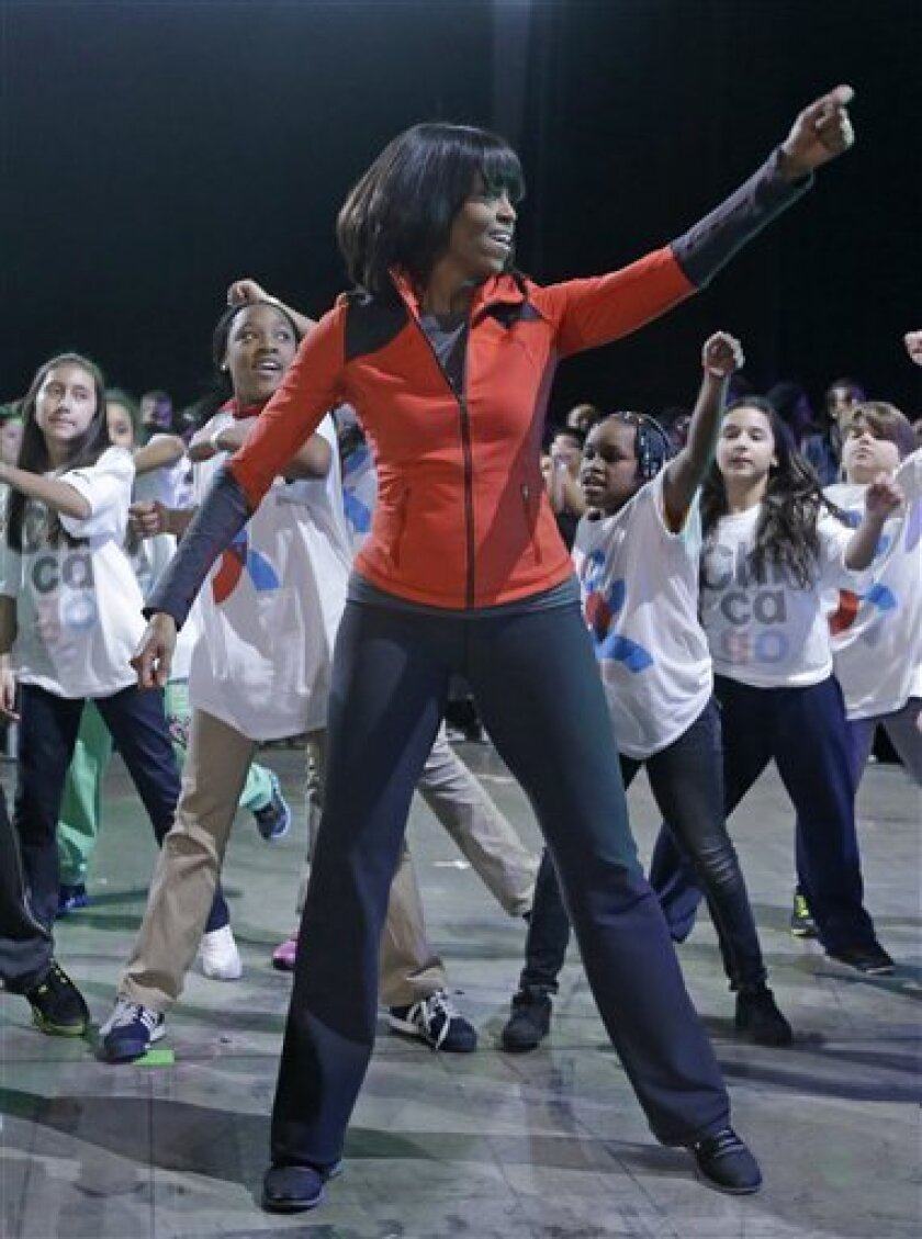 First lady Michelle Obama exercises with children from Chicago Public Schools, in her hometown of Chicago, Thursday, Feb. 28, 2013, as she makes a major announcement helping to bring back physical activity to area schools, while celebrating the third anniversary of her 'Lets Move' program.  (AP Pho
