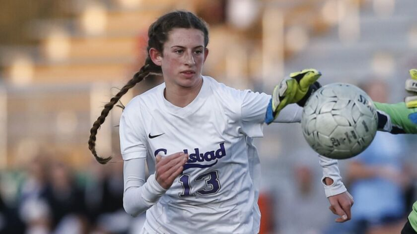 Carlsbad forward Lexi Wright (13) chases down a pass as OLP goalkeeper Grace Kotnik (0) makes a stop in the first half.