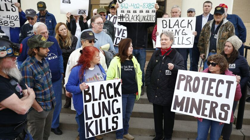 Coal mining advocates listen as Patty Amburgey of Letcher, Ky., speaks about the death of her husband from black lung disease during a protest near the office of Senate Majority Leader Mitch McConnell (R-Ky.) at the Laurel County Justice Center in London, Ky., Wednesday.