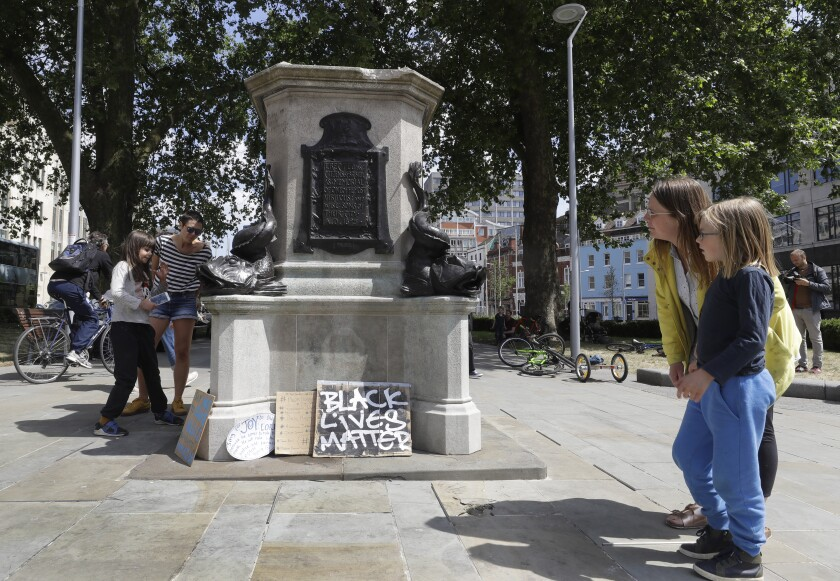 People look at the pedestal of the toppled statue of Edward Colston in Bristol, England, Monday, June 8, 2020, following the downing of the statue on Sunday at a Black Lives Matter demo. The toppling of the statue was greeted with joyous scenes, recognition of the fact that he was a notorious slave trader — a badge of shame in what is one of Britain's most liberal cities. (AP Photo/Kirsty Wigglesworth)