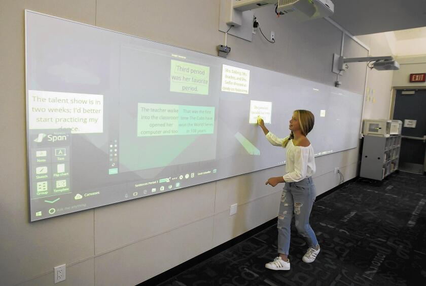 A student in sixth-grade English teacher Sarah Schaeffer's class at Thurston Middle School in Laguna Beach constructs a sentence using a Nureva board in the school's new-look library on Thursday.