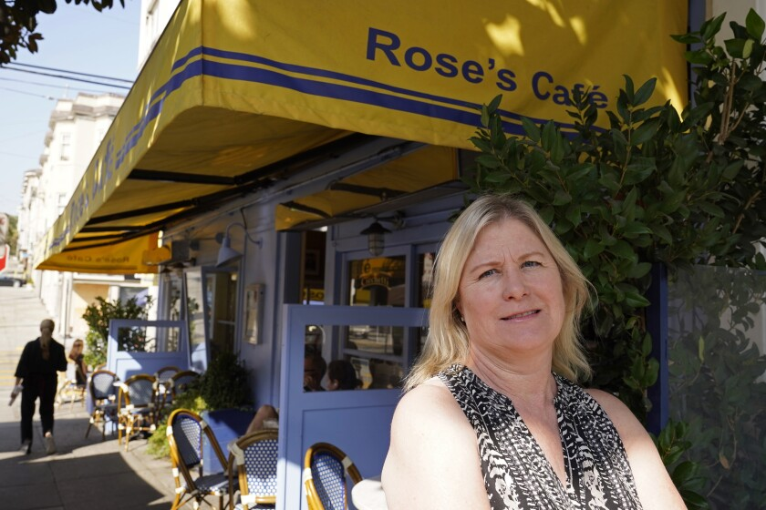 """FILE - In this Sept. 28, 2020 file photo, Laurie Thomas poses outside of her Rose's Cafe restaurant, Sept. 28, 2020, in San Francisco. California's landmark ballot measure that keeps a lid on property taxes by tying them to the most recent purchase price is facing one of the biggest challenges in its 42-year history. Proposition 15 on Tuesday's ballot would reassess commercial and industrial properties every three years. Thomas, who owns two restaurants in San Francisco, said Proposition 15 would be """"one more nail in the coffin"""" of her industry. (AP Photo/Eric Risberg, File)"""