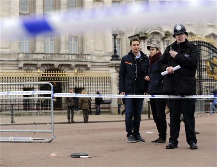 A cornered off area containing knives, a hat and Taser wire outside Buckingham Palace in central London after a man armed with two knives was stunned by police, Sunday Feb. 3, 2013. Scotland Yard said the man, thought to be in his 50s, acted aggressively when challenged by police outside the gates