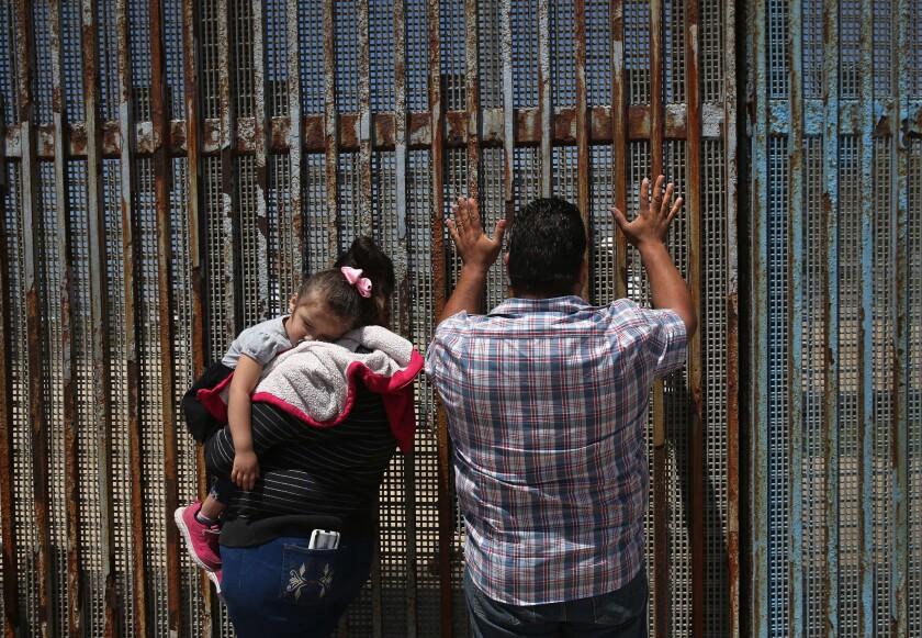 A family in Tijuana speaks to relatives through the U.S.-Mexico border fenc