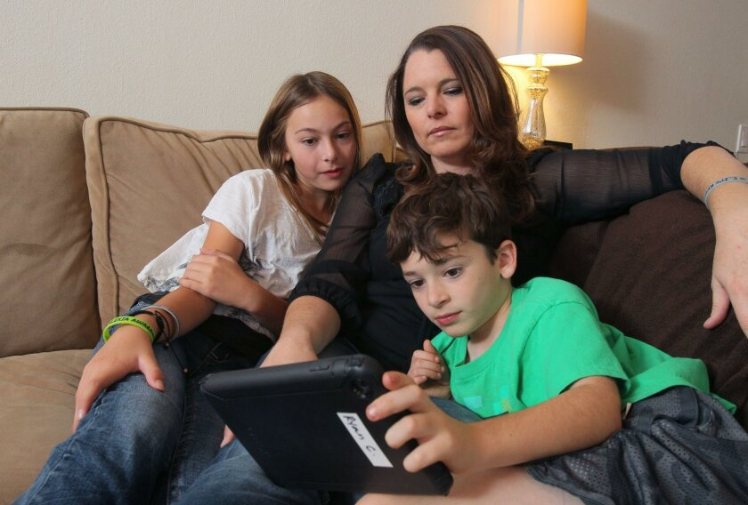 Stacey Cavaglieri helps her kids Ryan, 8, and Hailey, 11, use audiobooks to study reading. The kids have dyslexia.